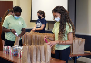 From left to right, Aniya Stewart, Kaylee Deardorff and Cassidy Richardson assemble lunches for Micah Ecumenical Ministries. Photo by Suzanne Carr Rossi.
